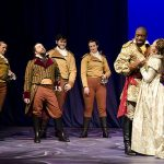 Othello and Desdemona embrace as soldiers look on