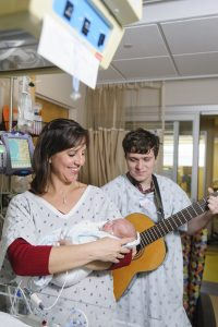 Andrea Cevasco-Trotter sings to a premature baby with one of her students.