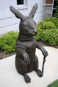 Bronze sculpture of a rabbit holding a cane