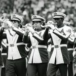 A row of band members perform in their 1970s uniforms.