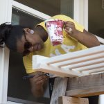 Student painting part of a house