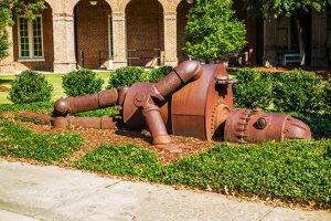 rusty robot statue laying down in a garden