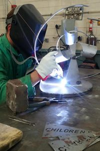 Allison Sloan welding her golf swing sculpture.