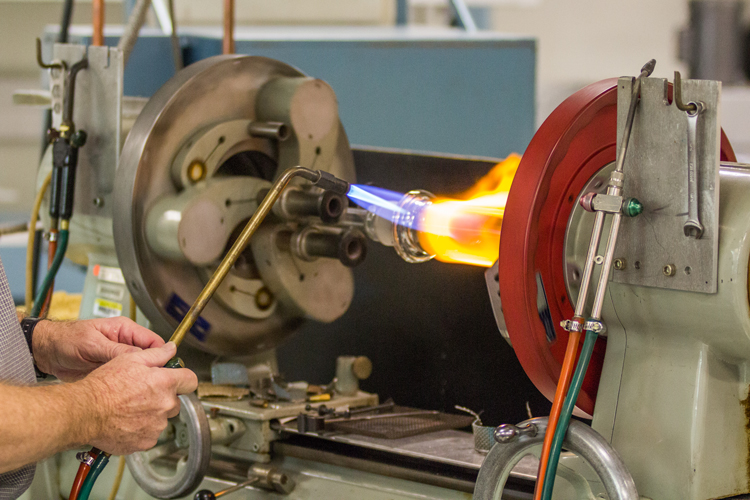 glassblower using a blowtorch to soften glass