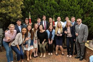 A group of students on the mock trial team hold two trophies