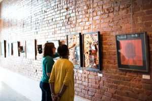 Two women observe art on the wall at the Paul R. Jones Museum
