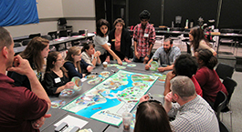 group of faculty and students surround a table and play the Watershed Game