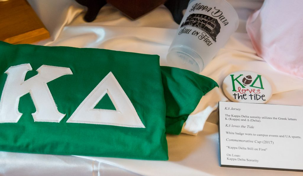 Green Kappa Delta jersey, commemorative cup, and button.
