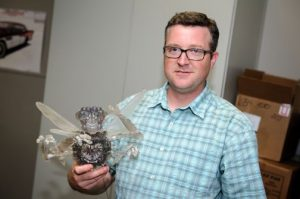 Jamey Grimes holding a small sculpture of a monster