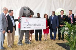 Several UA administrators and faculty take a group photo with Big Al holding a giant cardboard check for the UA United Way Campaign