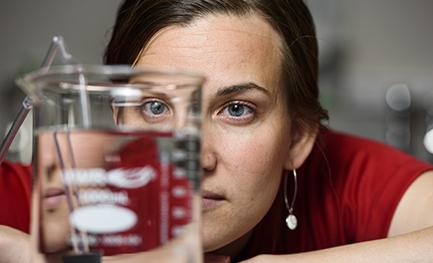 a woman looking at a beaker full of liquid
