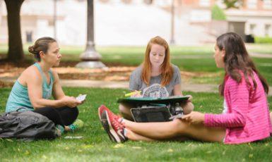three students sitting on the Quad