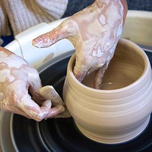 a student making a pot out of clay using a pottery wheel