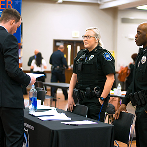 students talking with law enforcement officers about career opportunities