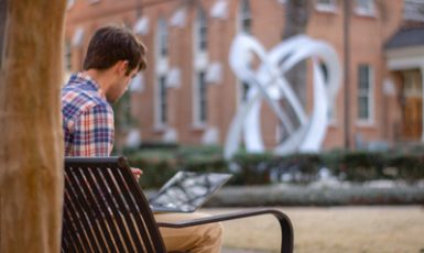 a student sitting on a bench in Woods Quad