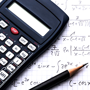 a calculator and pencil lying atop a notebook