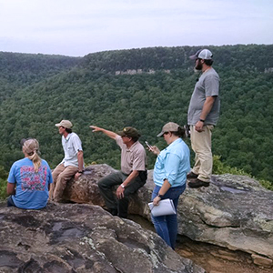 a group of students sitting on a high rocky cliff