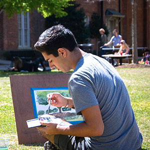 a student painting outside