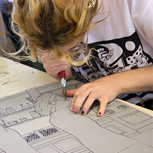 a student carving a printing block