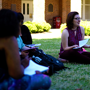 a group of students seated in Woods Quad, discussing a paper