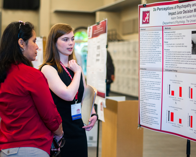 student presenting a poster at the annual research summit