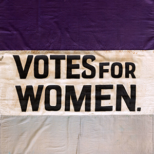 purple and gray flag that says Votes for Women