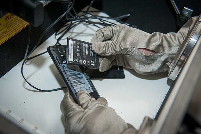 a gloved researcher examining cell phone components