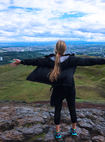 student with arms stretched over a cliff