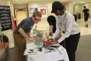 A student helps another student register to vote at a table.