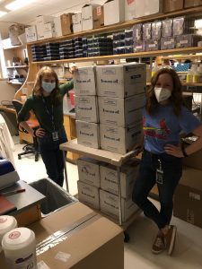 Two women wearing masks standing with several cardboard boxes.