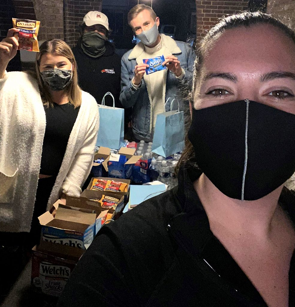 a group of college students standing around a table covered in goodie bags