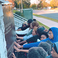 a group of students touching a monument