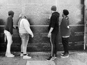 Students looking at stone monument with names