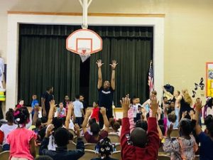 A dancer leads elementary students in a stretch.