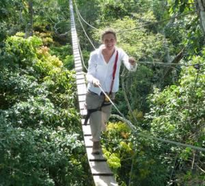 A woman crosses through a rainforest on a rope bridge