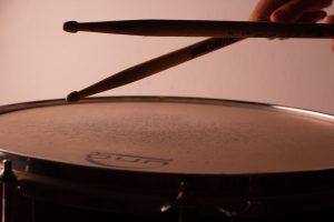 A drummer using sticks on a drum.