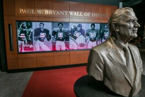 Paul Bryant bust in front of the Paul W. Bryant Wall of Honor in the Paul W. Bryant Museum