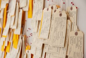 handwritten toe tags hanging on a wall